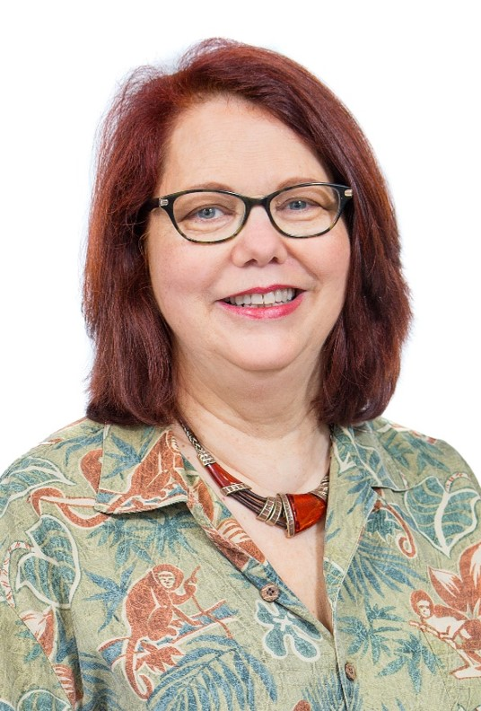 White woman with glasses and red hair. Aged 40-50